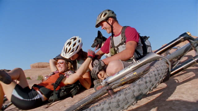 Medium shot one male and two female mountain bikers resting + laughing
