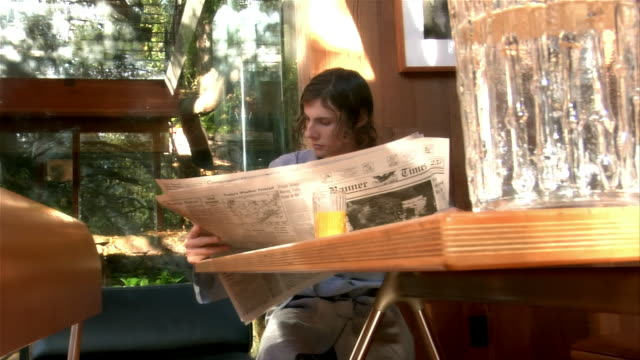 medium shot. one young man reading newspaper at table. - mid length hair stock videos & royalty-free footage