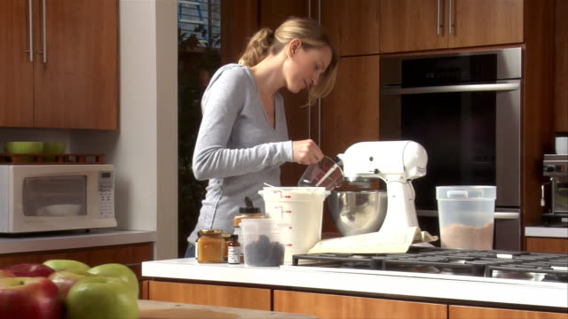 medium shot one young woman baking in kitchen - hushållsapparat bildbanksvideor och videomaterial från bakom kulisserna