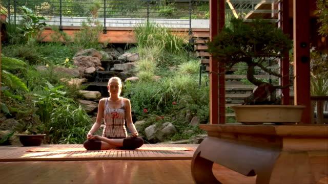 vídeos y material grabado en eventos de stock de medium shot. one young woman doing yoga on patio deck. - jardin