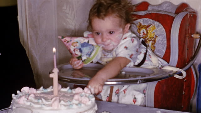 1952 medium shot one-year-old girl with cake on face reaching from high chair to grab and eat birthday cake