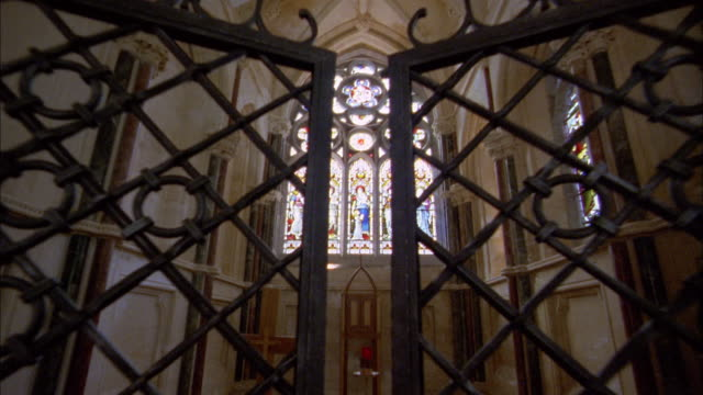 Medium shot opening gates to altar w/stained glass windows in church / Ireland