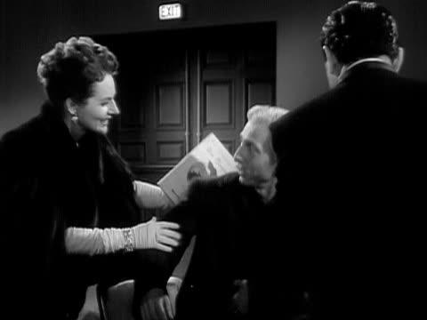 1951 medium shot opera singers jan peerce and nadine connor helping elderly man into his seat/ usa  - ソプラノ点の映像素材/bロール