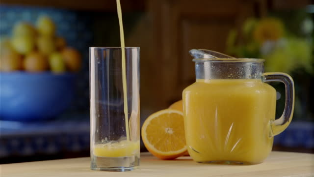 medium shot orange juice being poured into glass / pitcher and cut orange on table - jug stock videos & royalty-free footage