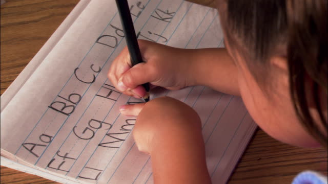 Medium shot over the shoulder view of student practicing her letters
