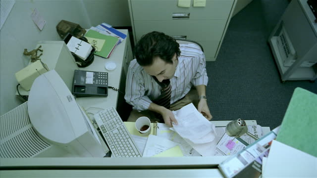 medium shot overhead view of man working and talking on phone in cubicle / spilling coffee on pants - office partition stock videos & royalty-free footage