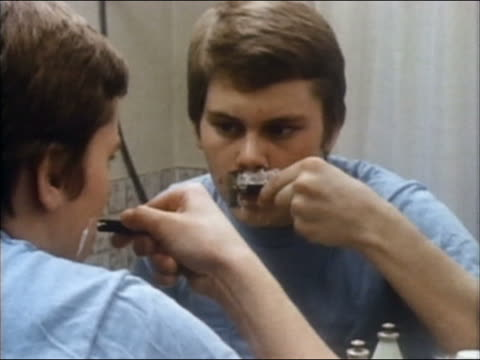 stockvideo's en b-roll-footage met 1985 medium shot over-the-shoulder adolescent boy looking in mirror and cutting himself shaving - tienerjongens