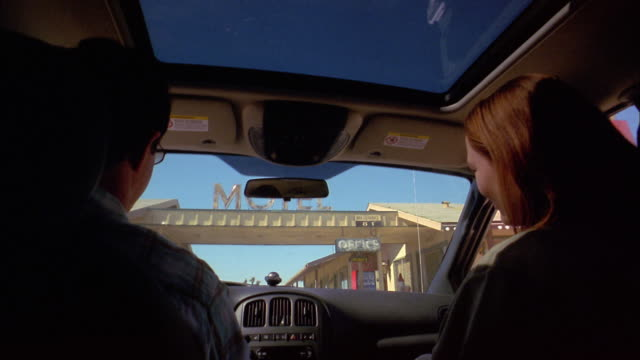 medium shot over-the-shoulder point of view of couple driving and approaching motel in moving vehicle - londonalight stock videos and b-roll footage