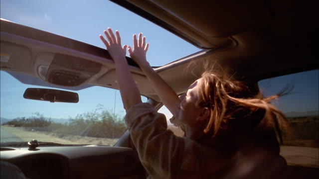 stockvideo's en b-roll-footage met medium shot over-the-shoulder point of view of woman stretching arms through sun roof in moving vehicle - 45 49 jaar
