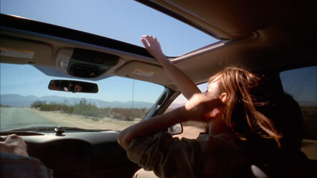 medium shot over-the-shoulder point of view of woman stretching arms through sun roof in moving vehicle - autoreise stock-videos und b-roll-filmmaterial