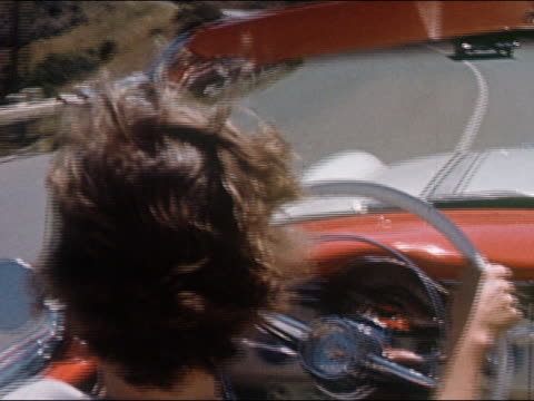 stockvideo's en b-roll-footage met 1956 medium shot over-the-shoulder shot of teenage girl driving convertible / hair blowing in wind / pan to water - 1956