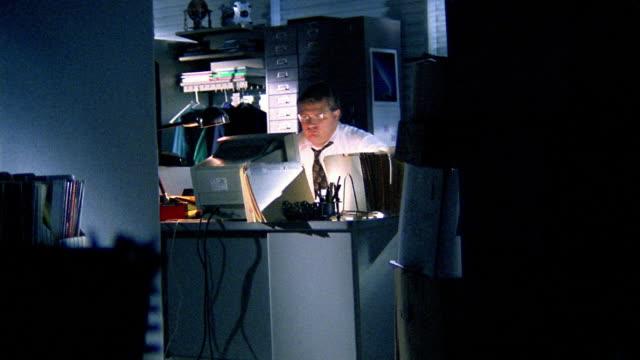 Medium shot overweight businessman stands up stretching behind desk after hours / walking away from desk