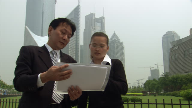 Medium shot pair of business people with skyscrapers in background looking at documents and pointing into sky/ Shanghai