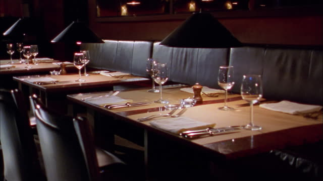 medium shot pan across empty restaurant tables w/wine glasses and place settings - テーブル点の映像素材/bロール