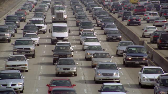 medium shot pan across lanes of heavy traffic on highway / los angeles, california - day stock videos & royalty-free footage