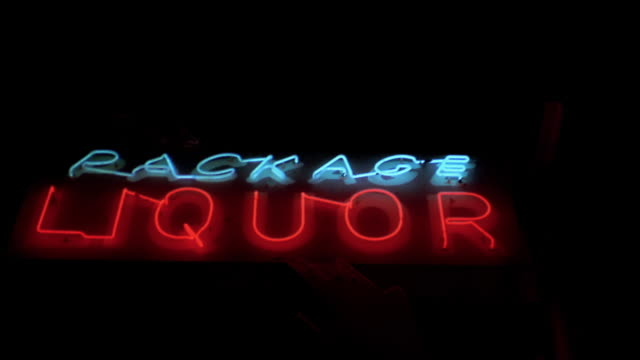 medium shot pan across neon red and blue 'package liquor' sign w/blinking arrow at night - blinking arrow stock videos & royalty-free footage