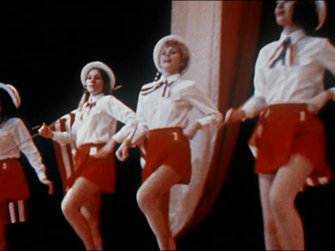 vídeos de stock e filmes b-roll de 1970 medium shot pan america's junior miss contestants dancing in patriotic outfits with american flags - patriotismo