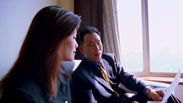 Medium shot pan Asian businesspeople meeting Caucasian businessman and shaking hands