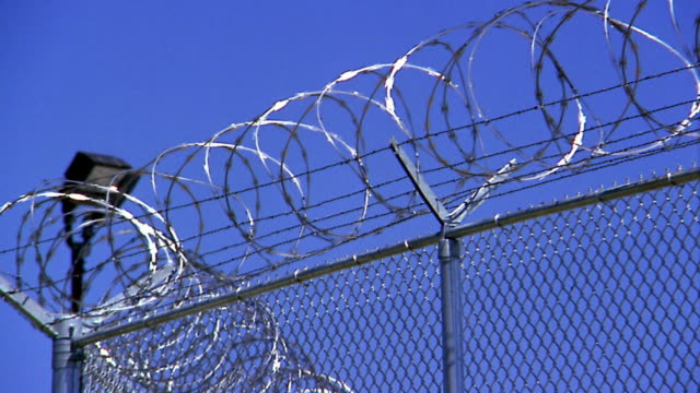 medium shot pan barbed wire atop chain link fence - fence stock videos & royalty-free footage