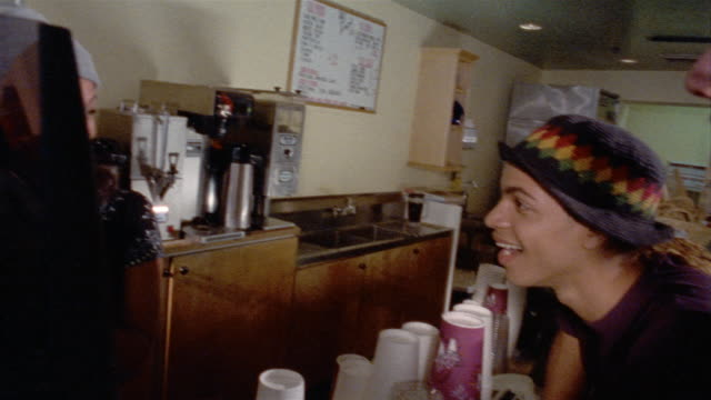 Medium shot pan barista talking to two young men at counter at cafe as she steams milk / serving them oversized mugs of coffee