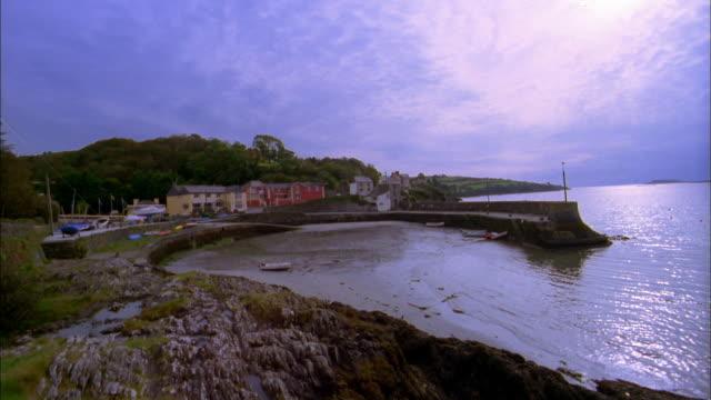 medium shot pan bay and coastline w/houses along shore / cork, ireland - 2002 stock videos & royalty-free footage