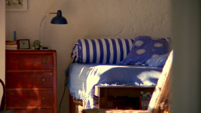 vidéos et rushes de medium shot pan bedroom interior from bed and dresser to open window / provence, france - domestic room
