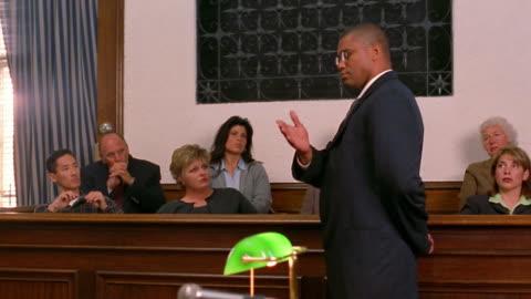 medium shot pan black lawyer talking to jury / paintiff in foreground - legal trial stock videos & royalty-free footage
