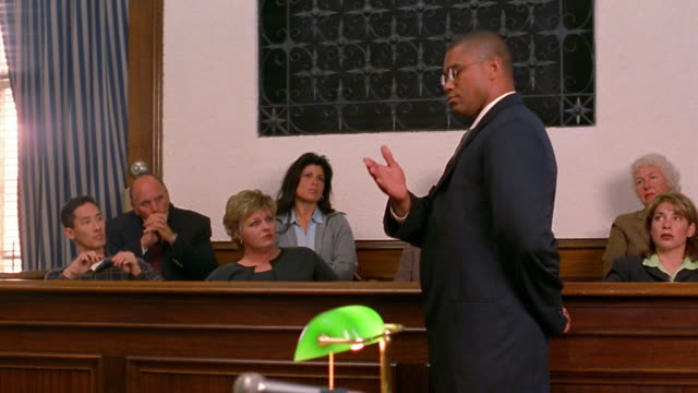 medium shot pan black lawyer talking to jury / paintiff in foreground - palazzo di giustizia video stock e b–roll