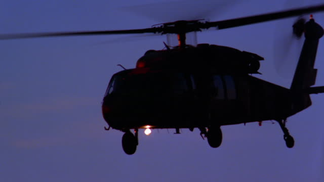 medium shot pan blackhawk helicopter flying by at dusk - black hawk helicopter stock videos and b-roll footage