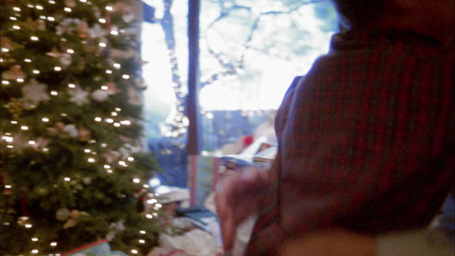 Medium shot pan boy smiling and hugging mother w/Christmas tree in background