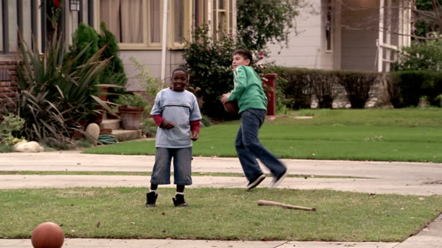 Medium shot pan boys tossing football back and forth in front yard
