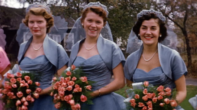 vídeos de stock, filmes e b-roll de 1953 medium shot pan bridesmaids to maid of honor to bride to groom to best men - bridesmaid