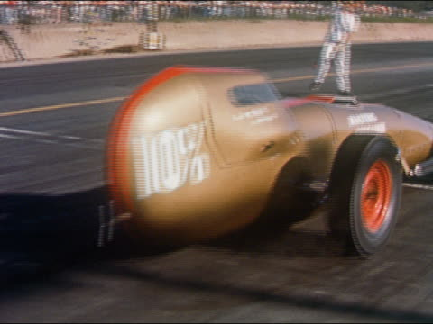 1959 medium shot pan bronze-colored race car taking off from starting line and speeding down race track