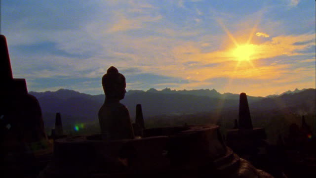 Medium shot pan Buddhist statue at Borobudur Temple with mountains and sunset in background / Java, Indonesia