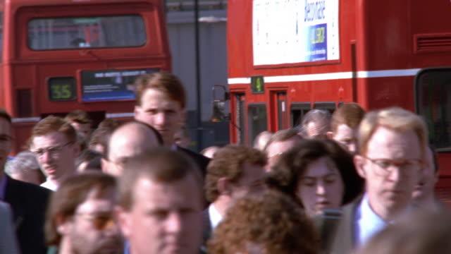 medium shot pan business crowds walking on sidewalk during rush hour in background / london - 2002 stock-videos und b-roll-filmmaterial