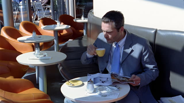 medium shot pan businessman drinking coffee at bar caroshi / berlin - magazine stock videos & royalty-free footage