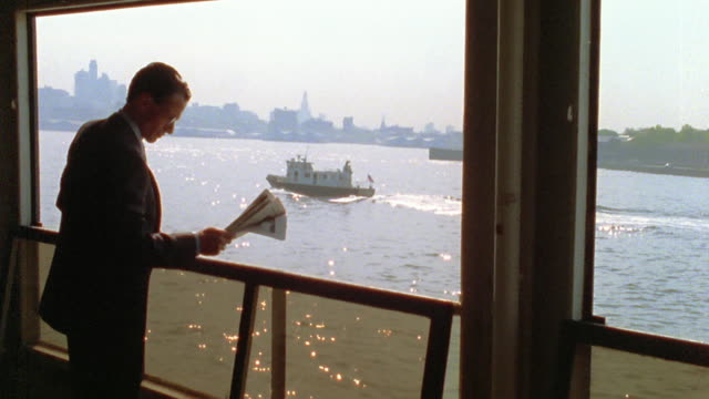 medium shot pan businessman reading newspaper on boat with tugboat, water and skyline in background / nyc - only mature men stock videos & royalty-free footage