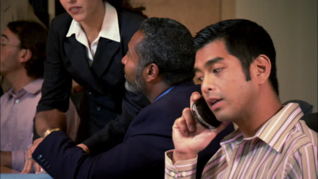 medium shot pan businesspeople talking and businessman using cell phone in conference room - ゴーティー点の映像素材/bロール
