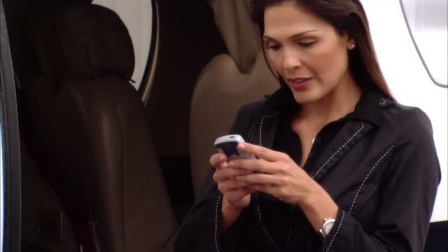 vídeos y material grabado en eventos de stock de medium shot pan businesswoman text messaging on mobile phone near private jet at opa locka airport/ miami, florida, usa - edificio de transporte