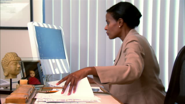 medium shot pan businesswoman using computer and looking through documents at desk in office - buddha stock videos & royalty-free footage