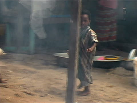 Medium shot pan child walking/ child approaching shack as woman cooks in a large pot on open fire/ Ghana