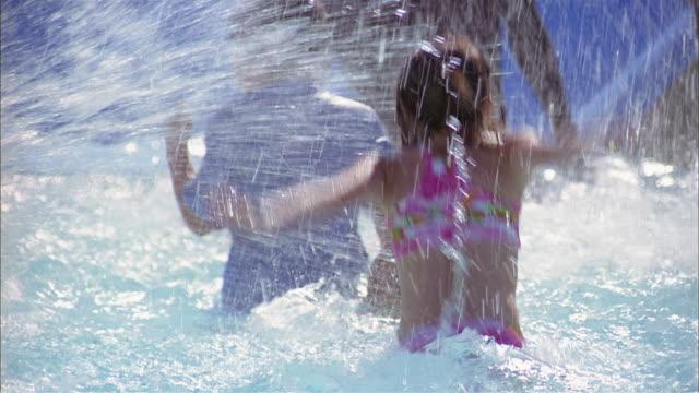 medium shot pan children splashing each other in pool - swimming pool stock videos & royalty-free footage