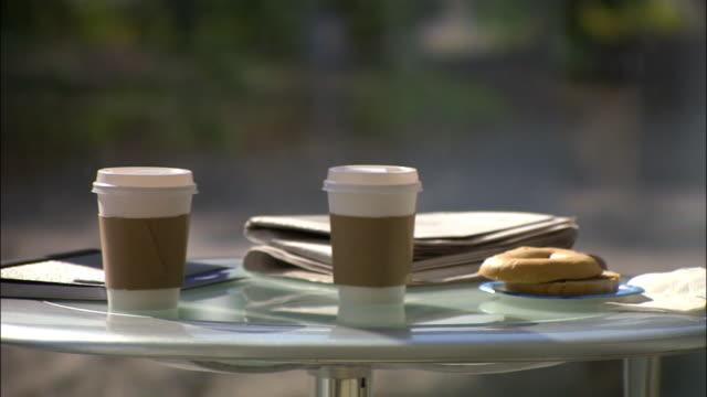 medium shot pan coffee cups, bagel, and, newspaper on table/ seattle - bagel stock videos & royalty-free footage