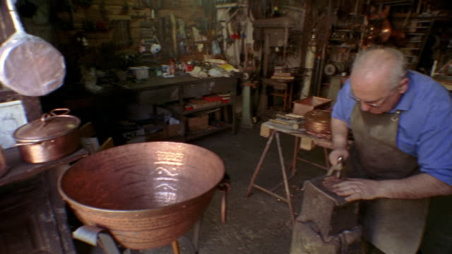 medium shot pan coppersmith working and looking up at cam in workshop in montepulciano / tuscany, italy - montepulciano stock videos & royalty-free footage