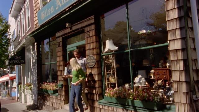 vídeos de stock, filmes e b-roll de medium shot pan couple leaving antique store / admiring clock and smiling - antiquário loja