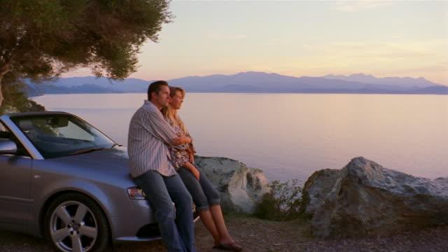 medium shot pan couple sitting on hood of car and enjoying view of water/ corsica - 年の差カップル点の映像素材/bロール