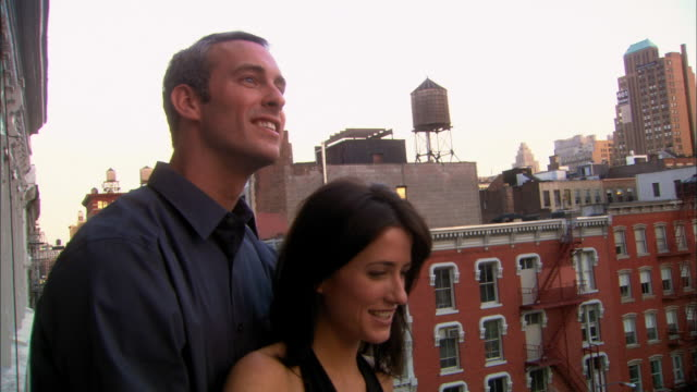 medium shot pan couple standing and hugging on balcony/roof overlooking city / nyc - breitwandformat stock-videos und b-roll-filmmaterial