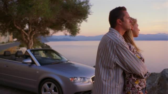 medium shot pan couple standing near car and enjoying sunset over water/ corsica - 年の差カップル点の映像素材/bロール