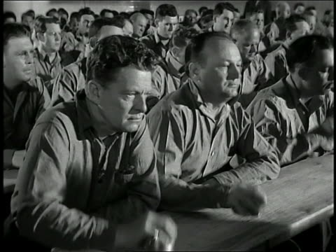 medium shot pan crowd of prisoners banging tin cups on tables - mob stock-videos und b-roll-filmmaterial