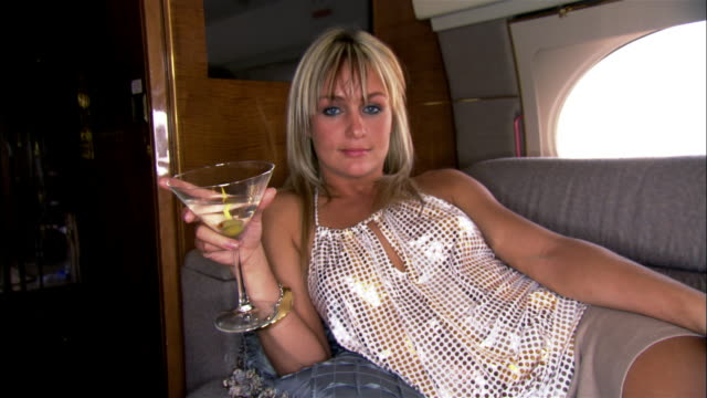 medium shot pan diva reclining and holding martini on private airplane - abitacolo video stock e b–roll